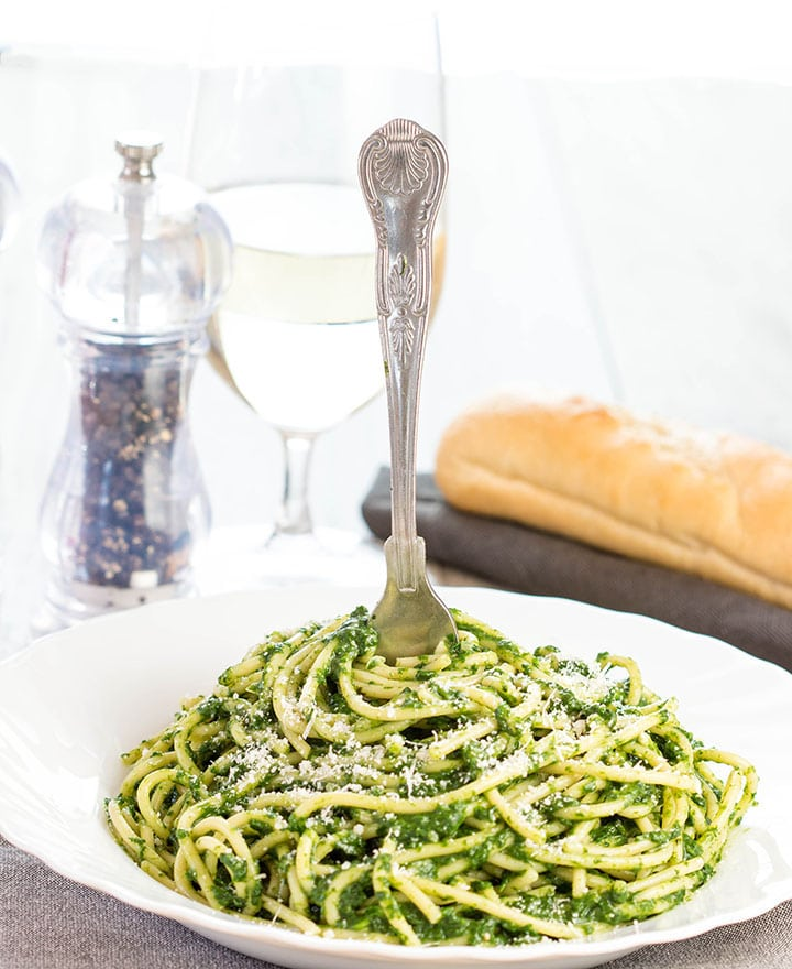 A bowl of Spaghetti with Spinach Sauce with a fork twirling the pasta around it.